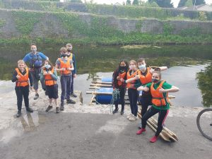 Scouts standing beside the raft they built